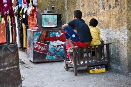 El CAIRO, Egipto - el 23 de julio Los niños sentados en el medio de la calle viendo la televisión, calles de bazar Khan El Khalili, un zoco principal en el distrito islámico, el 23 de julio de 2010, El Cairo, Egipto
