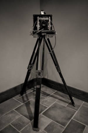 Old bellows camera standing over wooden tripod Stock Photo