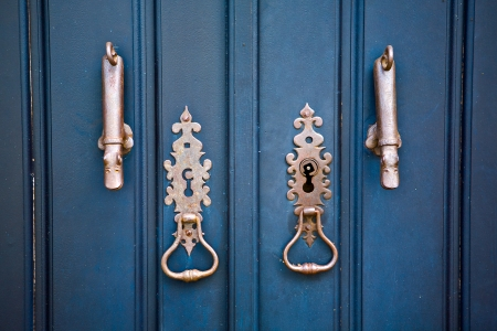 doorknocker: Iron doornockers over blue wooden door in Monsaraz, a medieval village on the right margin of the Guadiana River in Portuguese Alentejo region, near its border with Spain