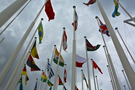 mundi: Flags of all nations of the world are flying in grey cloudy sky
