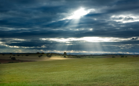 badajoz: Rural landscape, dramatic sky, and sun rays light over fields of Olivenza countryside, Badajoz, Extremadura, Spain Stock Photo