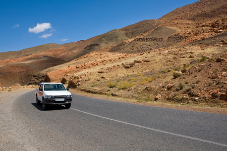 remoteness: Vehicle travelling on remote road with mountainous Draa Valley landscape in background, Morocco