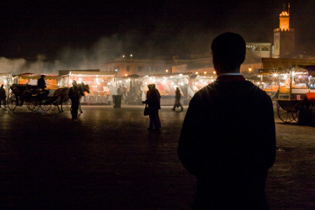 Unidentified man staring at food stalls  in Jemaa el Fna Square at dusk photo