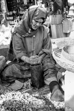 MARRAKESH - JANUARY 21  Old sitting woman making henna powder with mortar, Jan 21, 2010 Marrakesh, Morocco