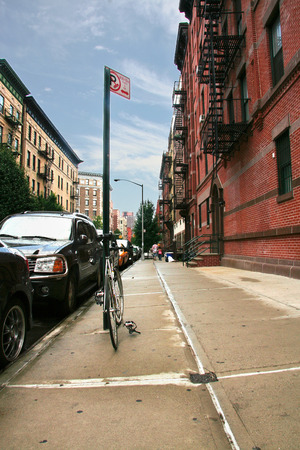 sideway: Silver bike chained on a traffiic sign in Harlem neighborhood sideway, New York