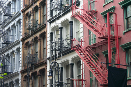 escapes: Four colorful, blue, brown, white and red apartment buildings facades with emergency escapes  Typical New York City rental complexes with fire escape stairs next to the windows