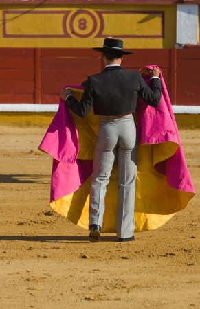 capote: The bullfighter waits the bull with the capote during a bullfight in Badajoz, Spain