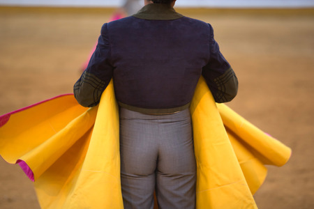 capote: The bullfighter wait the bull charge with the capote during a bullfight in Badajoz, Spain