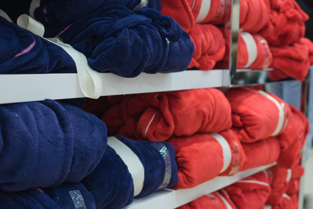 Piles of multicolored cotton clothing on the shelves of a fashion shop photo