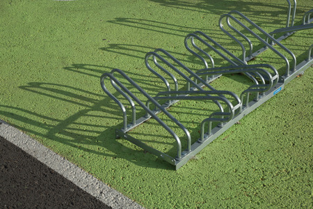Stainless steel bicycle empty racks over green asphalt surface Stock Photo