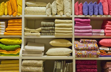 Almohadas brillantes, toallas, colchas, mantas y otra ropa para el hogar en los estantes Foto de archivo