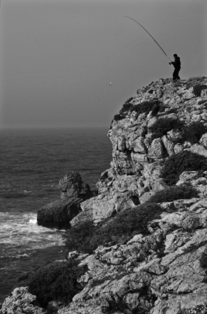 Man with fish and fishing-rod on sea background  at Sagres Cape cliffs, Portugal  photo