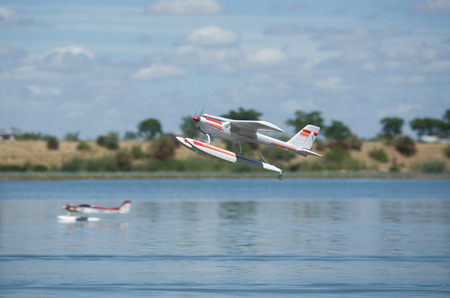 hydroplane: Radio controlled Hydroplane flying and sailing over the Guadiana river surface, Badajoz, Spain Stock Photo