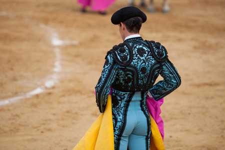bullfighter: The bullfighter wait the bull charge with the capote during a bullfight