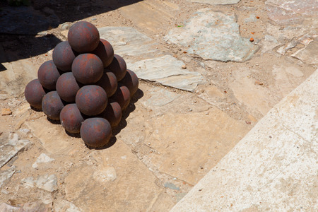 badajoz: San Cristobal Fort. Rusty cannon balls stacked in a pyramid, Badajoz, Spain