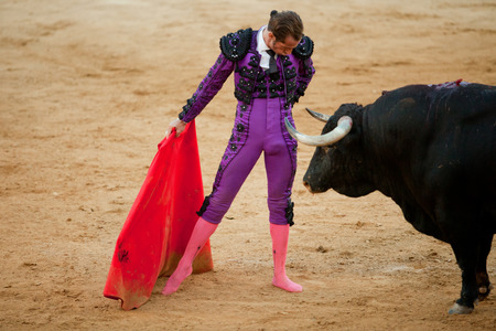 capote: BADAJOZ, SPAIN, JUNE 21  The  barefoot bullfighter waits the bull with the capote during a bullfight, on June 21, 2014 in Badajoz, Spain
