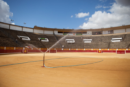 BADAJOZ, SPAIN, JUNE 21  Unidentified assistant irrigates the bullring sand in the morning before begin the bullfighting, on June 21, 2014 in Badajoz, Spain Banco de Imagens - 29630876