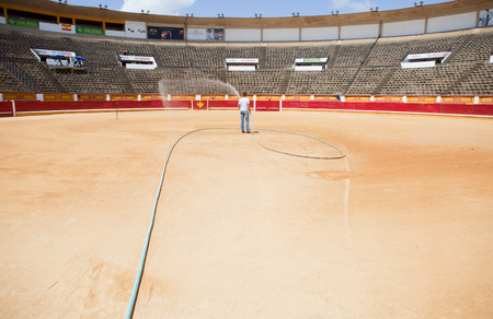 BADAJOZ, SPAIN, JUNE 21  Unidentified assistant irrigates the bullring sand in the morning before begin the bullfighting, on June 21, 2014 in Badajoz, Spain Editorial
