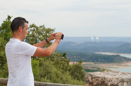GUADALAJARA, SPAIN  19 JULY  Unidentified cyclist taking pictures to spectacular landscapes of reservoirs of La Alcarria, with Trillo cooling towers of a nuclear power plant at the bottom, On july 19, 2014