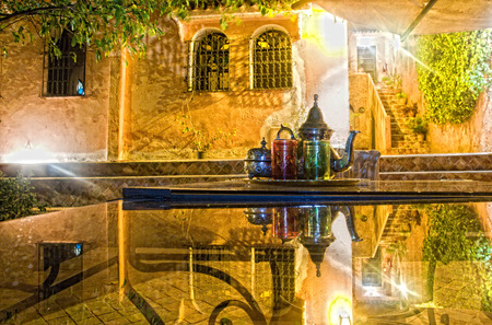 Moroccan tea party set up in a warm oriental candlelights atmosphere at night photo