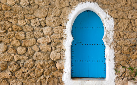 Traditional powder blue painted house facade and door in the historical Medina of Chefchaouen, Morocco  photo