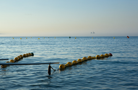 handrails: Handrails and Sunset Surfers in Ocean Waves, Ceuta, Spain Stock Photo