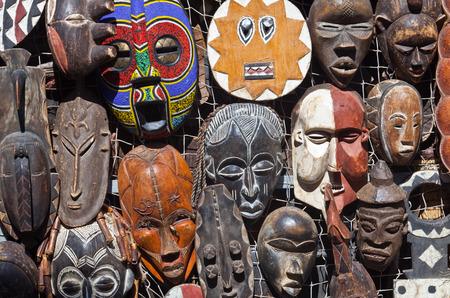 市場の屋台での掛かる伝統的なアフリカのマスクを販売します。