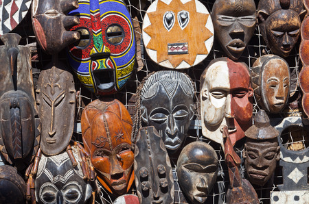 Traditional african masks hanging for sell in a market stall  photo