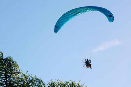 high powered: A powered paraglider pilot in flight with a blue clean sky in the background