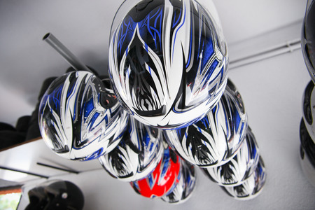 Go-Kart helmets hanging assorted. Karting circuit workshop photo