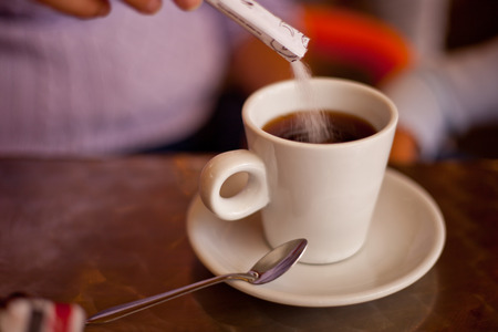 adding sugar: Adding sugar to his white ceramic cup on restaurant terrace table. Selective focus Stock Photo