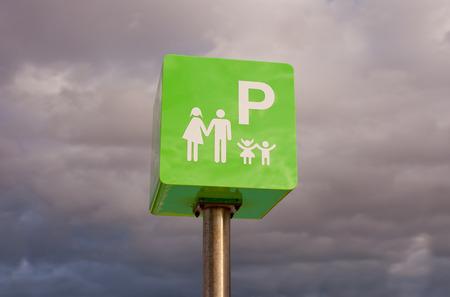 car care center: Reserved car park pole green sign for family against cloudy sky sky