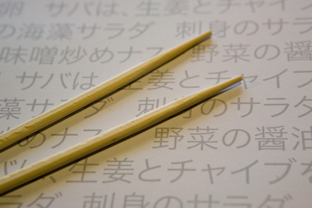 japanesse: Two brown wooden chopsticks on bamboo cover over Paper Table Mat of a restaurant with japanesse writting