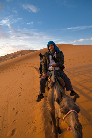A tourist ride the camel and admire the sunset from a hill. Several sand hill at Erg Chebbi in the Sahara desert.  Ers are large dunes formed by wind-blown sand. photo