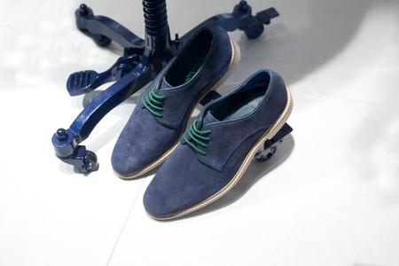manequin: Blue suede casual shoes over manequin metal stand Stock Photo