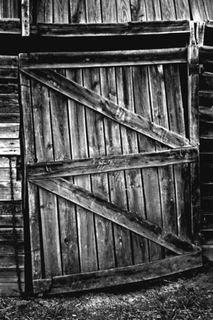 Weathered wooden door with rusty lock. Old farmhouse in Olivenza, Spain. Black and white. photo