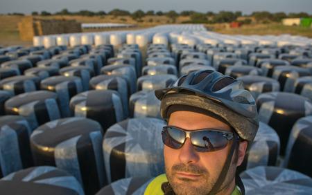 over packed: Autoritratto di ciclista uomo in piedi su rotoli di fieno imballato in plastica bianca
