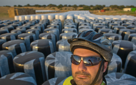 over packed: Self-portrait of cyclist man standing over packed hay rolls in white plastic