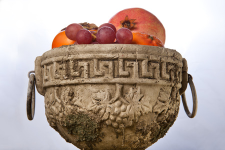 fretwork: Greek weathered fruit bowl with autumn fruits isolated over white background. Surface full of dry leaves Stock Photo