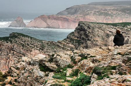 mujer mirando el horizonte: La mujer se sent� en el borde de los acantilados del Cabo San Vicente, Portugal