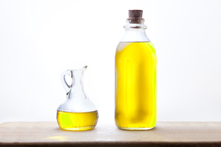 cruet: Olive oil bottle and cruet isolated over white background, placed on wooden surface Stock Photo