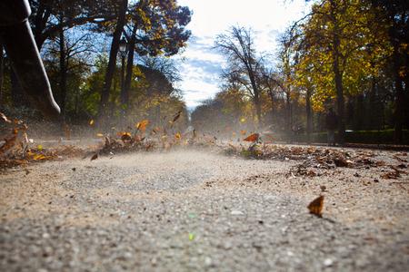 Trabajador en otoño con un soplador de hojas. Parque del Retiro, España