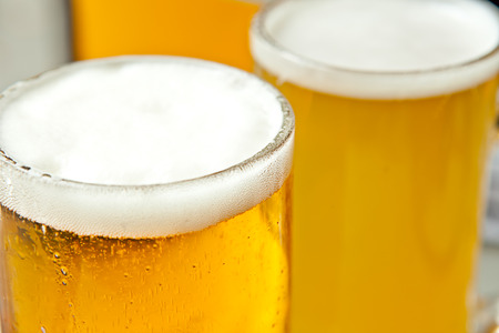 un bottled: Three glasses of fresh and foamy beer just served