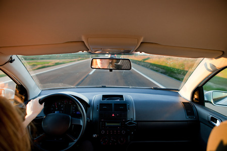 inside: Woman driving at sunset. Inside car view Stock Photo