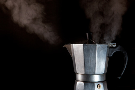 steam jet: Steaming expresso coffee maker at work isolated over black background
