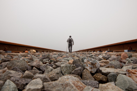 A man walking on the tracks with cane and trekking clothes a dense foggy day
