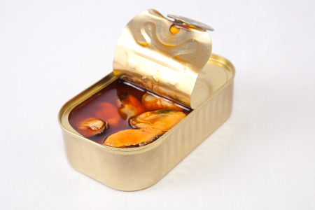 tinned goods: Mussels in a tin with a brown escabeche sauce of vinegar, oil and garlic. Isolated on white