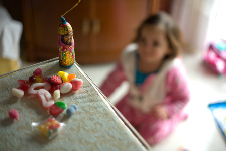 sweeties: Sweeties and Three Kings chocolate figurine while a toddler play with her new toys. Spanish tradition