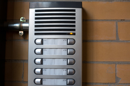 interphone: Intercom system at the entrance of a block of flats over bricks background