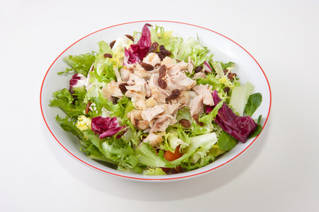 escarole: Chicken salad with tomatoes and raisin in a white bowl. Isolated over white background